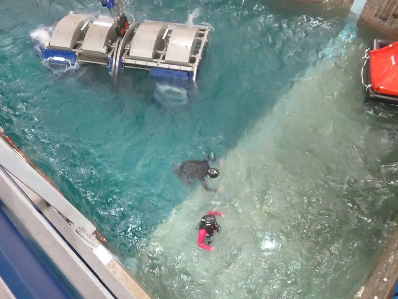 Водолаз (в черном цвете) помогает офшорному рабочему (в красном) в достижении безопасности спасательного плота справа от изображения. (Фото: Том Маллиган)