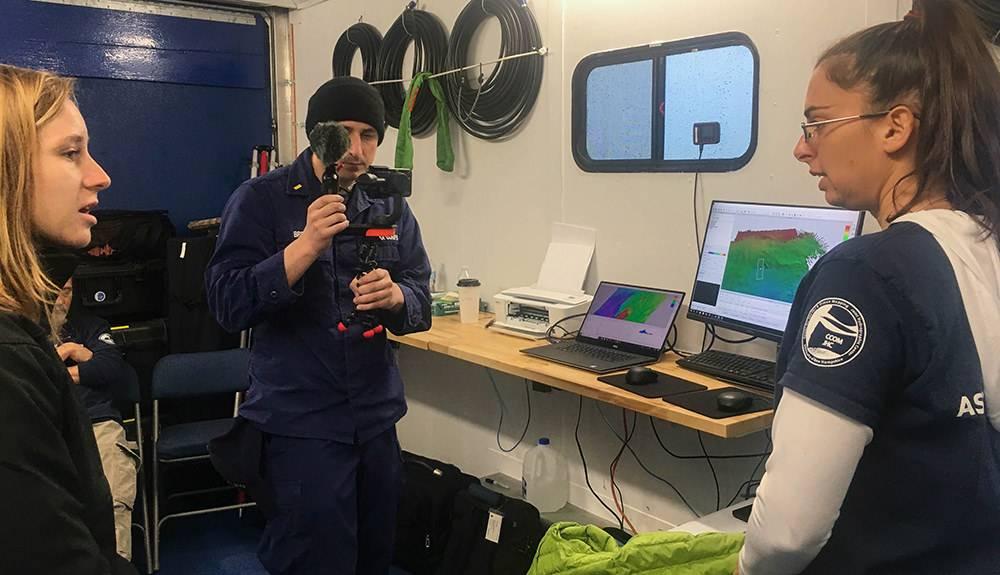 अभियान दल के दैनिक कार्यों का एक प्रमुख घटक शिक्षा और आउटरीच था, जिसे यहाँ दिखाया गया है क्योंकि टीम के सदस्य मिशन नियंत्रण वैन से सीधा प्रसारण करते हैं। लाइव प्रसारण में कक्षाओं के लिए और फेसबुक लाइव के माध्यम से सीधे कनेक्शन शामिल थे। आप राष्ट्रीय समुद्री अभयारण्यों के फेसबुक पेज के कार्यालय के माध्यम से संग्रहीत प्रसारण देख सकते हैं। (फोटो: ओशन एक्सप्लोरेशन ट्रस्ट)