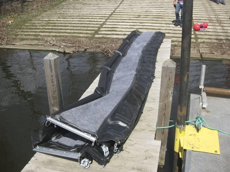 25-футовая секция внутреннего подводного нефтяного барьера выложена на доке до развертывания в понедельник, 23 апреля 2018 года, в Каламазу, штат Мичиган. Трехфутовый барьер из ПВХ и ткани X-Tex предназначенный для пропускания воды при улавливании масла. Взвешенные цепи и заслонки препятствуют просачиванию нефти и осадков под барьером. (Фотография береговой охраны США предоставлена Центром исследований и разработок)