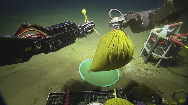 Durchschneiden der Tasche, um Glasperlen im Caisson freizugeben (Copyright: 2018 ONC / OET / Nautilus Live)