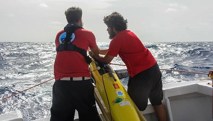 Grant Rawson de la NOAA (izquierda) y Luis O. Pomales Velázquez de la Universidad de Puerto Rico en Mayagüez se preparan para desplegar un planeador. (Foto: NOAA)