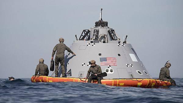 Taucher der US Navy assistieren der NASA und der USS Anchorage holen eine Mock-up-Kapsel zurück, die grob die Größe, Form, Masse und den Schwerpunkt des Orion-Crew-Moduls simuliert, das nach der für Dezember geplanten Exploration Mission-1 im Pazifik planschen wird. 2019. (US Navy Foto von Abe McNatt)