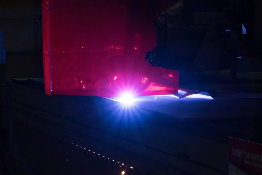 Uma máquina de queima de plasma corta a primeira placa de aço que será usada para construir o submarino de mísseis balísticos Columbia (SSBN 826). Foto de Matt Hildreth / HII
