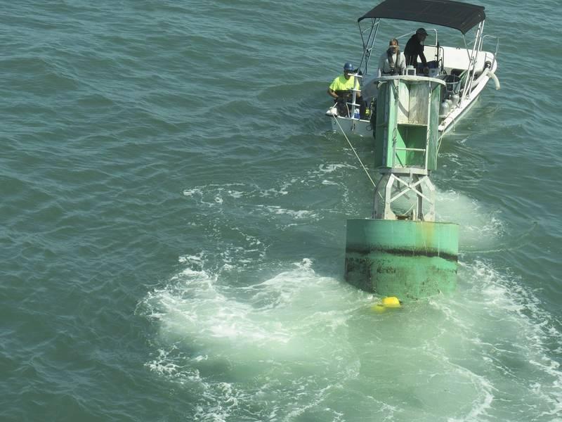 Un bote de buceo lleva una boya con una línea de amarre ecológico a los buzos que esperan sujetarla a uno de los anclajes (Foto cortesía de la Guardia Costera de los EE. UU.)