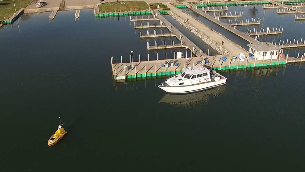 La tormenta R / V de NOAA espera a que ASV BEN abandone el puerto deportivo de Rogers City para iniciar las operaciones de mapeo en el Lago Huron durante la expedición. (Foto: David Cummins / Alpena Community College)