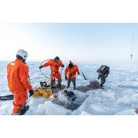 Figure 2. Diver attempting to locate mooring under ice. (Photo credit: Daniel Fatnes of the Norwegian Coast Guard)