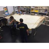 Investigators examine piece of aircraft debris (Photo: ATSB)