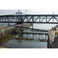 Personnel from the U.S. Army Engineer Research and Development Center and U.S. Geological Survey watch as a 350-ton crane lowers the 105-foot-long weldment, or underwater acoustic deterrent system, into the lock approach of Lock 19 near Keokuk, Iowa, Feb. 3, 2021. Laboratory-tested sounds that proved to be irritating to invasive Asian carp will be broadcast underwater from the weldment as part of a study to evaluate fish behavior. (U.S. Army Corps of Engineers photo)