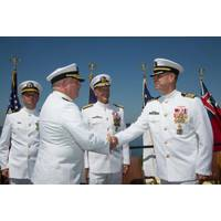 Rear Adm. Michael Jabaley (second from left) shakes hands with Rear Adm. (select) Moises DelToro (right) as they pass command of the Naval Undersea Warfare Center from Jabaley to DelToro.  Looking on are Vice Adm. William Hilarides, commander of the Naval Sea Systems Command (second from right) and Lieut. Philip Carson, Naval Station Newport chaplain (left).