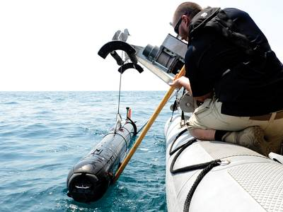 A civilian contractor steadies a M18 Mod 2  Kingfish Unmanned  Underwater Vehicle (UUV) as it is lifted with a crane onto the deck of an  11-meter rigid-hull  inflatable boat.  (U.S. Navy photo by Mass Communication Specialist 2nd Class Blake Midnight/Released)
