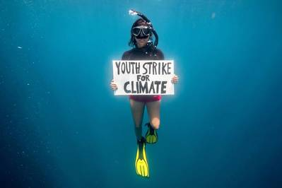 Climate activist Shaama Sandooyea holds a placard reading 'Youth Strike For Climate' in support of the climate strike movement. During an underwater protest in the Saya de Malha bank in the Indian Ocean. (© Tommy Trenchard / Greenpeace)