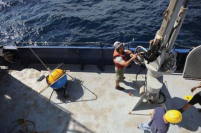 Crew aboard the Office of Naval Research (ONR)-sponsored research vessel (R/V) Melville retrieve a wave buoy during an at-sea demonstration of the Environmental & Ship Motion Forecasting (ESMF) program.