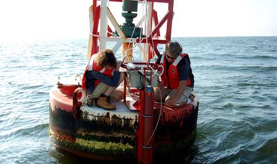 Max Ivanov and Scott Mowery with NOAA's Center for Operational Oceanographic Products and Services install an improved current sensor system on a navigation buoy in Chesapeake Bay. The system transmits real-time current speed and direction observations via satellite to help mariners more safely navigate busy shipping channels. (Photo: NOAA)