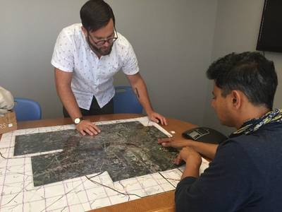 Jeremy Hoffman, scientist with the Science Museum of Virginia, (standing) and Vivek Shandas, professor at Portland State University, pore over a map of Richmond, Virginia, as they plan the routes for citizen scientists to collect heat data with a special sensor tool attached to their cars. The data will then be used to create a high-resolution map of the city's hottest neighborhoods, which will provide information for cooling projects, tree planting and other climate action strategies. Photo cou