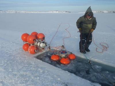 Joey Angnatok preparing ADCP and IPS mooring cages for deployment through the ice.   (Photo credit: James Barlett)