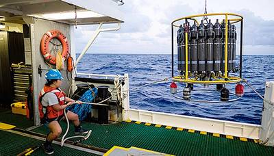 A marine technician hauls in the CTD (conductivity, temperature, and depth) rosette on a research cruise in the Sargasso Sea. © Maya Thompson
