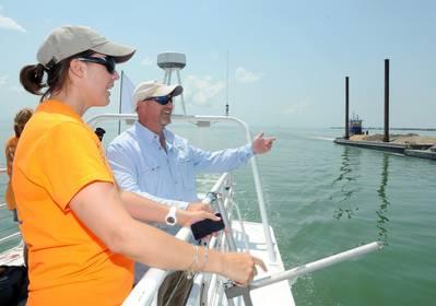 Rearchers point towards barge: Photo courtesy of Island Univ.