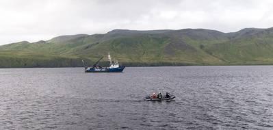 एक गोताखोर टीम रिमस 100 एयूवी के माध्यम से एकत्र किए गए सोनार लक्ष्यों की जांच करती है, आरवी नॉर्समन II पृष्ठभूमि में नौकायन (फोटो: एनओएए)