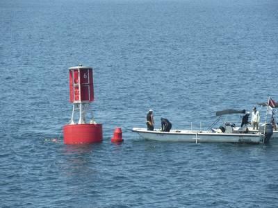 潜水员准备在水下将系泊绳固定到其锚上(照片由美国海岸警卫队提供)