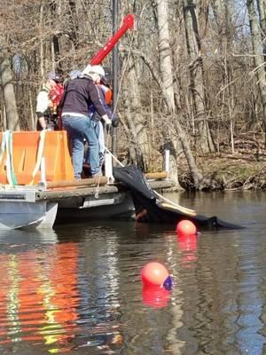 2018年4月25日星期三,研究人员使用绞车从密歇根州卡拉马祖河上取回一段水下石油屏障系统。填充沙子的塑料交通路障阻挡了河底的屏障系统,同时系泊浮标标记了测试。 (美国海岸警卫队照片由研发中心提供)