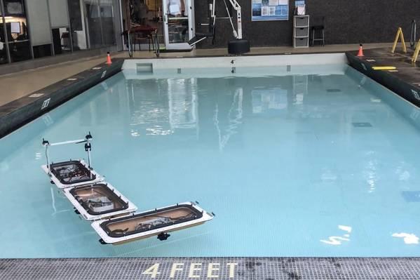 """麻省理工学院的机器人船队已经更新了""""变形""""的新功能,通过自动断开和重新组装成不同的配置,在阿姆斯特丹的运河中形成各种浮动平台。在游泳池的实验中,船只从连接的直线重新排列成""""L""""(此处显示)和其他形状。图片来源:麻省理工学院"""