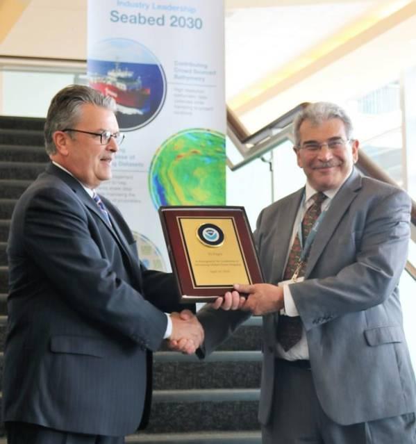 De izquierda a derecha: Craig McLean de NOAA presenta a Edward Saade de Fugro con una placa conmemorativa en reconocimiento formal del liderazgo de la compañía en el avance del mapeo global del océano (Foto: Fugro)