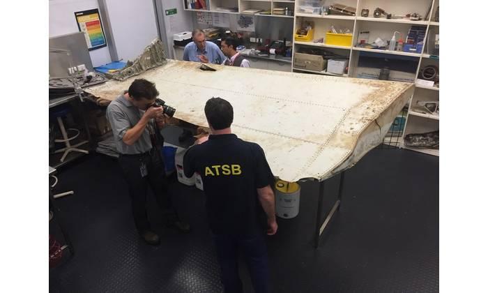 Investigators examine piece of aircraft debris (Photo: ATSB)