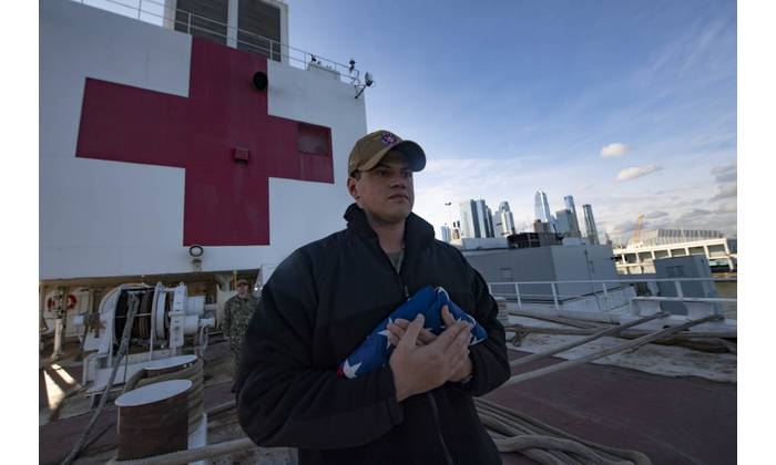 U.S. Navy file photo of Aviation Boatswain's Mate 2nd Class Justin Cosgrove participating in morning colors aboard the hospital ship USNS Comfort (T-AH 20) while the ship is moored in New York City in support of the nation™s COVID-19 response efforts. (U.S. Navy photo by Mass Communication Specialist 2nd Class Sara Eshleman)
