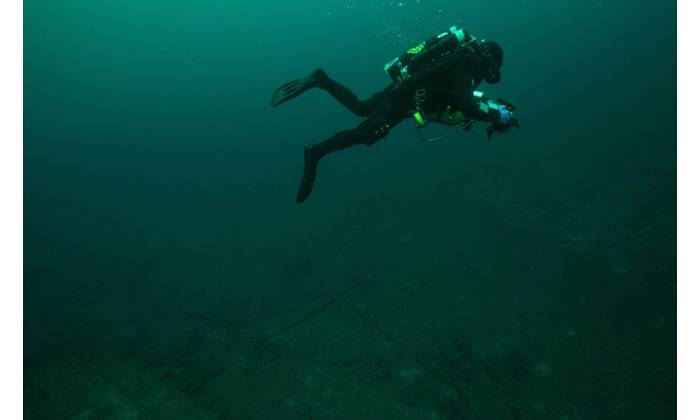 Phase IV started with a series of 'work-up' dives used to practice technical diving techniques and refine the photogrammetric imagery acquisition protocols before visiting deeper sites. Here, NOAA Diver Joe Hoyt swims above the debris field off the stern of wooden bulk carrier New Orleans. He maintains a consistent altitude off the bottom, necessary to ensure broader coverage of the debris field features as the relate to the main vessel remains. (Credit: NOAA, Thunder Bay National Marine Sanctua