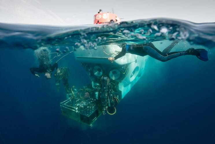 Atlantis crew members Patrick Neumann and Allison Heater assist in the recovery of Alvin following a test mission. They attach safety lines to support Alvin's payload basket before it is lifted from the water. (Photo by Chris Linder, Woods Hole Oceanographic Institution)