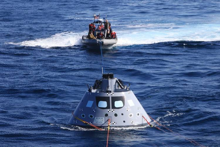 Boats carrying Navy divers and NASA's recovery team guide the capsule to the USS Anchorage as the ship safely operates on station (Photo: NASA)