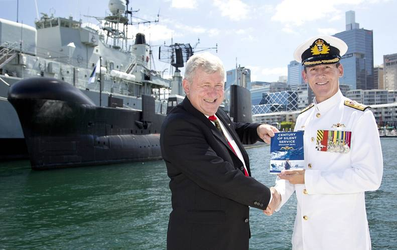 "Commodore Peter Scott, CSC, RAN is handed a copy of the book ""Century of Silent Service"" from one of the authors, Mr Lloyd Blake. (Photo: Tom Gibson)"