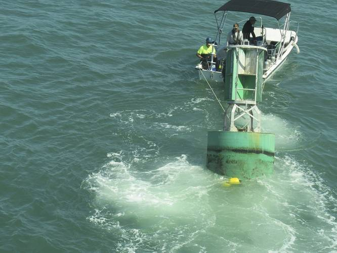 A diver boat tows a buoy with attached eco-mooring line toward divers awaiting to fasten it to one of the anchors (Photo courtesy of the U.S. Coast Guard)