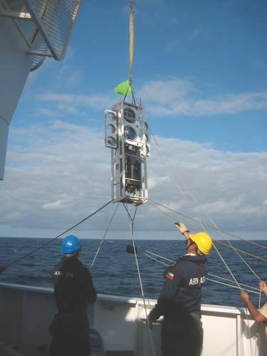Figure 2: The benthic lander Audacia is raised over the side for deployment by the deck crew of the modern Chilean scientific vessel Cabo de Hornos, operated by the Chilean Armada.  The glass spheres put bouyancy high, while the instruments put the weight low, creating inherent stability. (Image: Courtesy Kevin Hardy and Atacamex 2018)