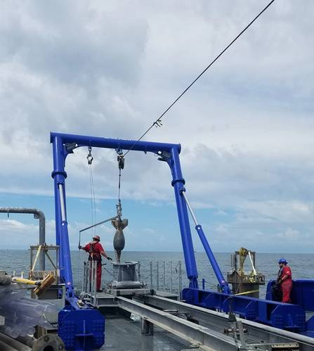 Figure 2 – The piston coring rig deployed over the stern, and just prior to sampling. Image courtesy of A. Evans.