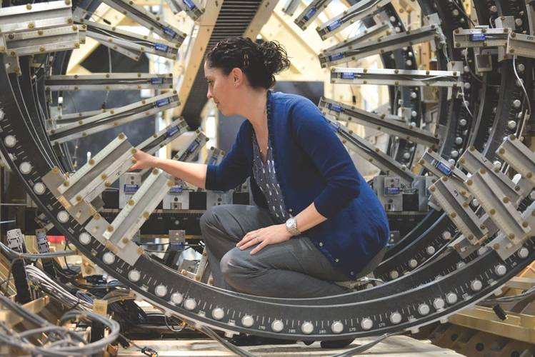 Jessica McElman, an electrical engineer at Naval Surface Warfare Center, Carderock Division, adjusts a magnetic field sensor in the model track located in the Magnetic Fields Laboratory in West Bethesda, Md. (U.S. Navy photo by Nicholas Malay)