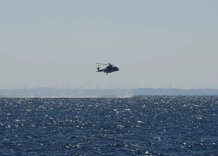 A JMSDF MCH-101 mine warfare helicopter rakes for mines in Mutsu Bay during 2JA 2017 Mine Countermeasures Exercise (2JA-17 MCMEX). 2JA Mine Countermeasures Exercise is an annual bilateral exercise held between the U.S. Navy and Japanese Maritime Self Defense Force to strengthen interoperability and increase proficiencies in mine countermeasure operations. (Photo by William McCann)