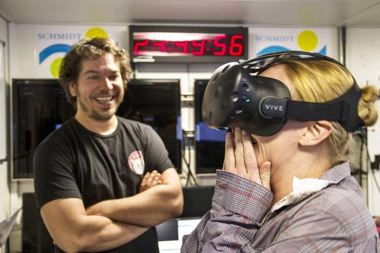 Ben Knorlein, Computer Scientist, observers Melissa Omand as she reacts to the first Virtual Reality experience created on board Falkor from holographic images of plankton suspended in the water. (Photo: SOI/ Mónika Naranjo González)