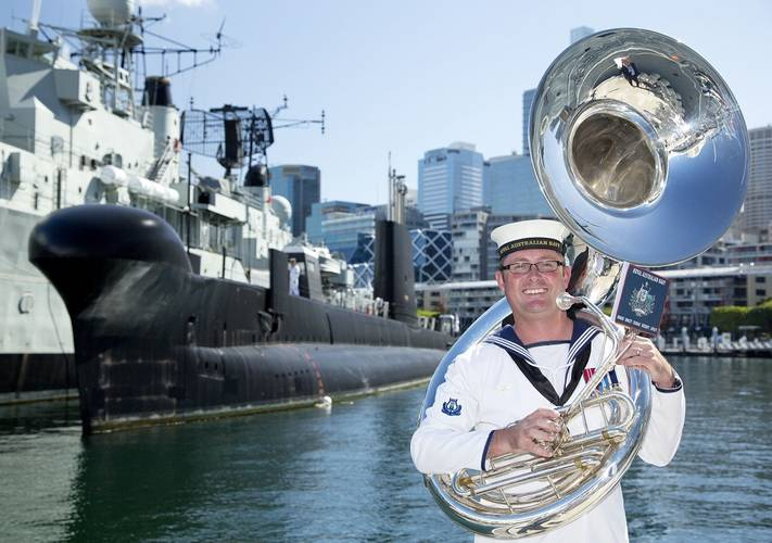 "Musician Leading Seaman Martyn Hancock who composed the musical piece ""March of the Silent Service"" stands in front of decommissioned submarine HMAS Onslow at the Australian National Maritime Museum, Darling Harbour, Sydney. (Photo: Tom Gibson)"
