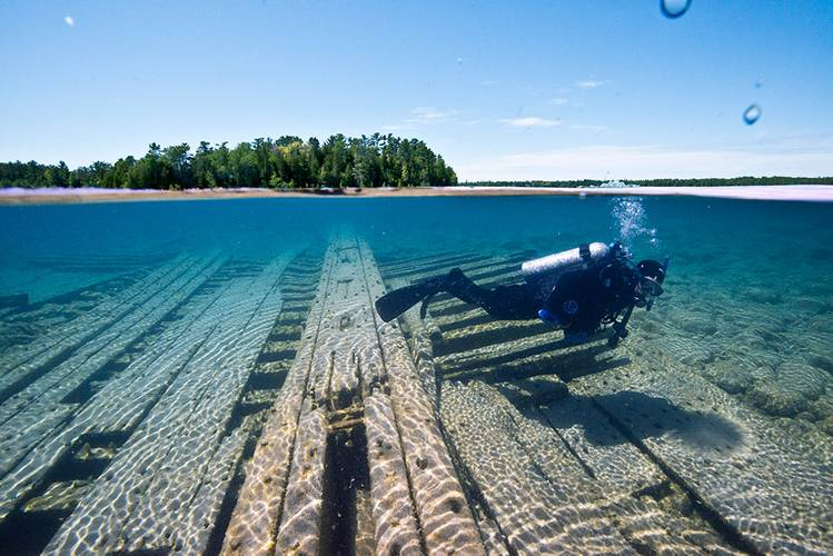 A NOAA diver swims over the shipwreck site of the wooden two-masted schooner Portland within Thunder Bay National Marine Sanctuary. (Photo: NOAA)