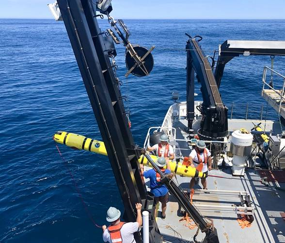 AUV Recovery: AB Peter Brill, AB Chris Remaley, GVA Sidney Dunn, and Acting CB Michael Collins recover the REMUS 600 using the J-frame on the CTD deck of the Okeanos Explorer. Image courtesy of Charlie Wilkins.