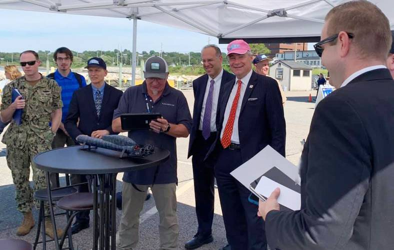 Rhode Island Secretary of Commerce Stefan Pryor (center, from left) and U.S. Sen. Sheldon Whitehouse get a demo on the latest swarming technology from Aquabotix during the Advanced Naval Technology Exercise (ANTX) 2019 held on Aug. 29 at the Naval Undersea Warfare Center Division Newport. (by Public Affairs Officer Jeff Prater)