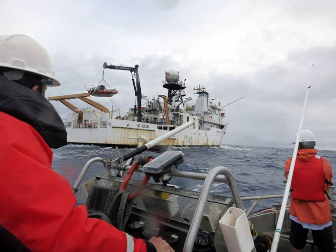 A small boat approaches the NOAA Ship Hiʻialakai, as another boat that just returned is carefully placed in its 'cradle' with a crane. (Photo: NOAA Fisheries)