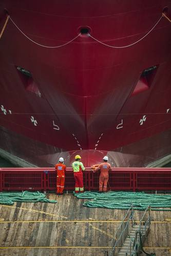 DOF subsea workers stand on the deck facing the hull of a massive DOF Subsea offshore vessel.  (Photo courtesy of DOF Subsea)